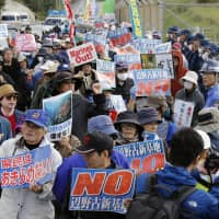 Protesters opposed to the plan to move U.S. Marine Corps Air Station Futenma from Ginowan to Nago, both within Okinawa Prefecture, stage a rally in front of Camp Schwab in Nago on Friday. | KYODO