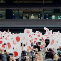 People wave Hinomaru flags as they celebrate Emperor Akihito's 85th birthday while being greeted by members of the Imperial family at the Imperial Palace in Tokyo on Sunday. It was the last official birthday ceremony held for the Emperor, who plans to abdicate on April 30. | RYUSEI TAKAHASHI