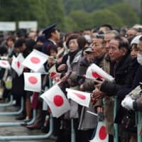 People wait to catch a glimpse of Emperor Akihito on his 85th birthday. | RYUSEI TAKAHASHI