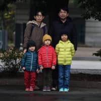 Masahiro and Kiyoko Higuchi brought their three sons to the Emperor's birthday celebration on Sunday 'to witness history.' | RYUSEI TAKAHASHI