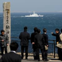 Japan Coast Guard vessel PS08 Kariba sails off Cape Nosappu in Nemuro on Hokkaido , with part of the Russian-held islands visible the background, in 2017. | REUTERS
