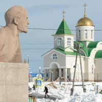A bust of Soviet state founder Vladimir Lenin is seen in front of a Russian Orthodox church in Yuzhno-Kurilsk on the Island of Kunashiri, one of four islands known as the Southern Kurils in Russia but claimed by Japan, 2016. | REUTERS