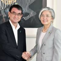 Foreign Minister Taro Kono (left) and his South Korean counterpart Kang Kyung-wha shake hands before talks on July 8 in Tokyo. | KYODO