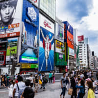 People walk in Osaka's Shinsaibashi downtown area. The Kansai region faces a long list of tasks from next year on — from the Group of 20 summit meeting to the 2025 World Expo, both of which will be hosted by Osaka.   GETTY IMAGES