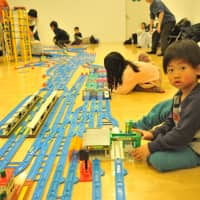 Children play with Plarail, a railway construction kit produced by toy-maker Takara Tomy, at Purafesu on Saturday.   ANDREW MCKIRDY