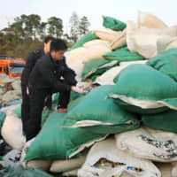 Police inspect smuggled recyclable waste in Nanning, southern China, last February. | COURTESY OF CNS / ‹KYODO