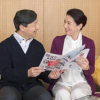 Crown Princess Masako and Crown Prince Naruhito look at a booklet at the Togu Palace, the couple's official Tokyo residence, on Dec. 4. | IMPERIAL HOUSEHOLD AGENCY / VIA KYODO