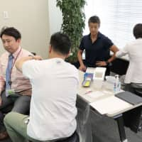 Male employees are immunized against rubella at the Tokyo branch of Osaka-based Rohto Pharmaceutical Co. in November. | ROHTO PHARMACEUTICAL CO. / VIA KYODO