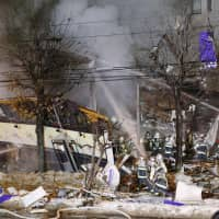 Firefighters try to put out a fire following an explosion at a restaurant in Toyohira Ward, Sapporo, on Sunday evening. | KYODO