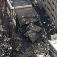 The remains of a wooden building are seen Monday after an explosion and fire at the building in Sapporo on Sunday night. | KYODO