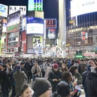 People throng the famed 'scramble crossing' in Shibuya Ward, Tokyo, on the night of Dec. 31, 2016. It was made a pedestrian-only area late at night on Dec. 31 for the first time in 2016. | KYODO