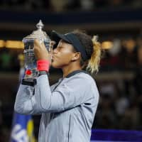 Naomi Osaka kisses the trophy after winning at the U.S. Open in New York in September. | KYODO