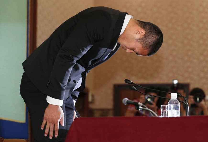 Nihon University defensive end Taisuke Miyagawa bows deeply on May 22 at the Japan National Press Club, where he apologized for an illegal tackle and revealed he was forced to make the controversial play by his coach, Masato Uchida.
