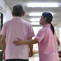 A foreign caregiver takes care of a man at a nursing center in Tenri, Nara Prefecture, in May 2017. | KYODO