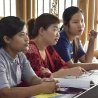 Myanmar women planning to go to Japan as foreign trainees and work as caregivers study Japanese at a school in Yangon in May. | KYODO