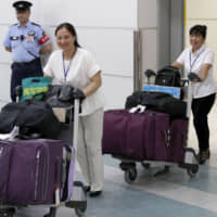 Two Chinese women under the foreign trainee program for nursing care arrive at Fukuoka Airport in July. | KYODO