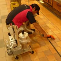 A cleaning staff member uses a newly developed vomit-cleaning vacuum. | JR EAST ENVIRONMENT ACCESS CO.