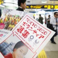 Leaflets to recruit volunteers for the 2020 Tokyo Olympics are handed out at Shinjuku Station in September. A resolution encouraging volunteerism that was co-sponsored by Japan was adopted Monday by the U.N. General Assembly. | KYODO