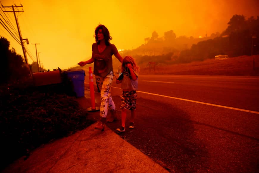 A mother and son walk along a California highway as the Woosley fire threatens their Malibu home. Many were quick to draw a connection between the fires in the area, which have been steadily increasing, and global climate change.