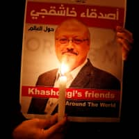 A demonstrator outside the Saudi Arabian consulate in Istanbul holds a poster of Saudi journalist Jamal Khashoggi who was allegedly killed and dismembered inside the consulate. | REUTERS