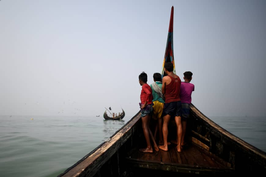 Rohingya refugees crew a fishing boat in the Bay of Bengal near Cox