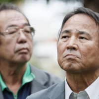 Hiroji Yamashiro, right, attends a gathering organized by his supporters Thursday in Naha, Okinawa Prefecture, after the high court ruling upheld a lower court verdict against him. | KYODO