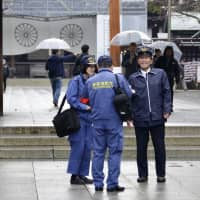 Officials from the Fire and Disaster Management Agency inspect Yasukuni Shrine in Chiyoda Ward, Tokyo, on Dec. 12, following a small fire incident due to a protest. | KYODO
