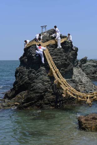 Hanging out: Teams of volunteers change the shimenawa (sacred rope) of Meoto Iwa in Mie Prefecture.