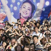 Star struck: Fans of J-pop star Namie Amuro pose in front of her image in Ginowan, Okinawa Prefecture, in September ahead of her final concert. | KYODO