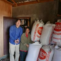 Untapped wealth: Katsuhisa Ota (left) with a stockpile of unsold coffee beans he discovered in the Philippine region of  Mindanao. | KATSUHISA OTA