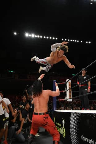 Wrestler Hiroshi Tanahashi dives on top of Jay White during a New Japan Pro-Wrestling event at Tokyo