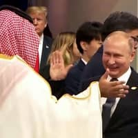 Russian President Vladimir Putin and Saudi Crown Prince Mohammed bin Salman greet each other at the Group of 20 summit in Buenos Aires on Nov. 30 as U.S. President Donald Trump looks on. | AFP-JIJI