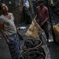 Workers weigh bowls of coal at a coal wholesale market in Mumbai. India is making a gradual shift away from fossil fuels, but coal is also getting a renewed push as a cheap source of energy. | BLOOMBERG