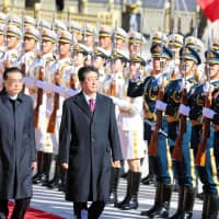 Prime Minister Shinzo Abe reviews a military honor guard with Chinese Premier Li Keqiang  during a welcome ceremony outside the Great Hall of the People in Beijing on Oct. 26. | KYODO