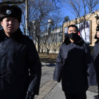 Police patrol in front of the Canadian Embassy in Beijing on Dec. 13. | AFP-JIJI