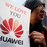 Lisa Duan, a visitor from China, shows her support for Huawei CFO Meng Wanzhou in  Vancouver, British Columbia, on Monday.  | REUTERS