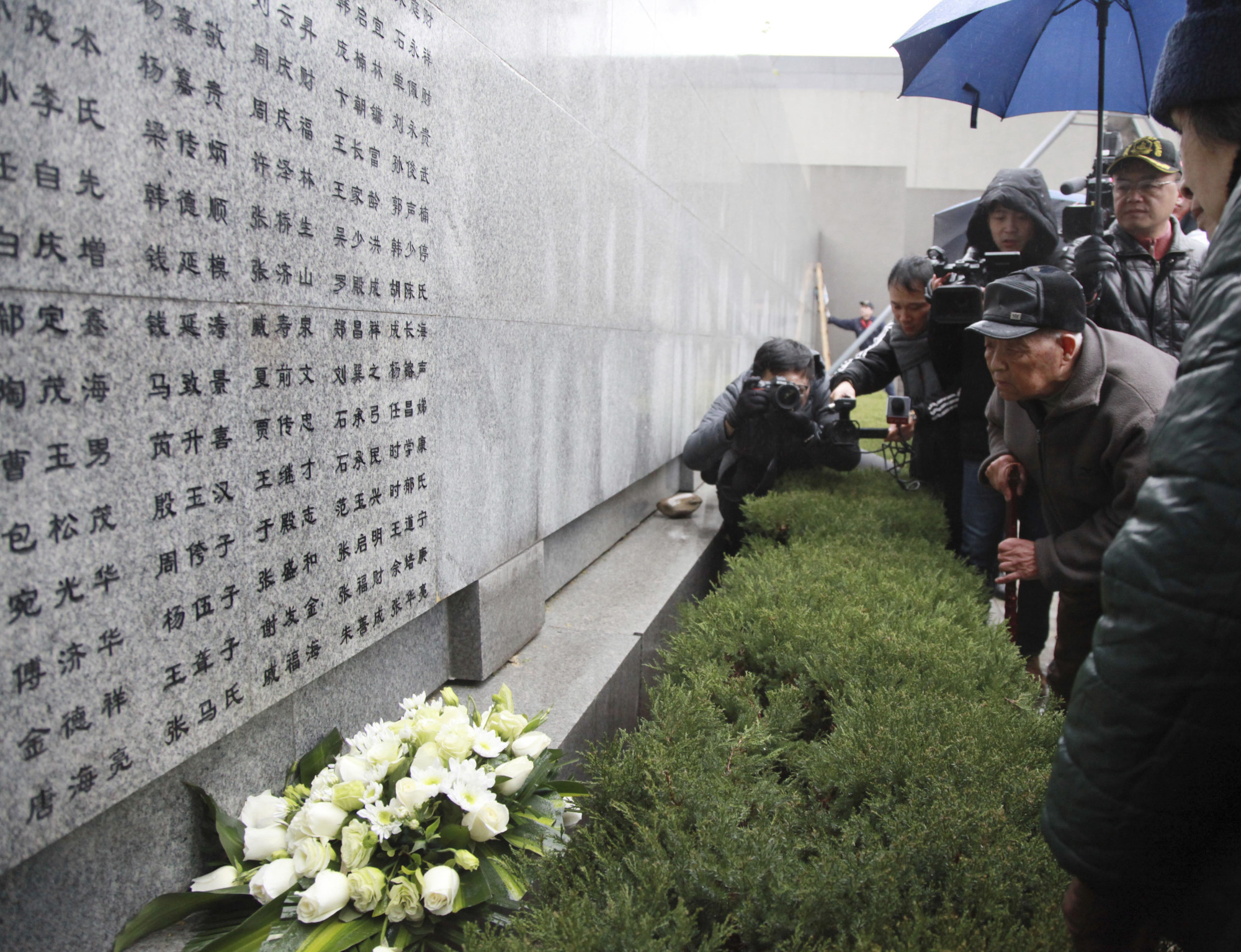 A man mourns a relative whose name was recently added to the memorial wall in Nanjing on Dec. 10. The wall  now contains the names of 10,664 confirmed victims. | YAO JUN — IMAGINECHINA