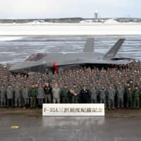 Air Self-Defense Force personnel pose with their first operational F-35A at Misawa Air Base in Aomori Prefecture on Jan. 26. | AIR SELF DEFENSE FORCE