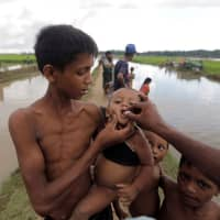 Rohingya refugees who crossed into Bangladesh the previous day from Myanmar receive cholera vaccines while they await permission to continue to refugee camps on Oct. 17, 2017. | REUTERS
