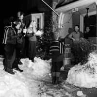 A family in Canada entertains their neighbors in 1955 by going door to door, singing Christmas carols in the snow. | PHOTOGRAPHER: EVANS/HULTON ARCHI