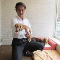 Akira Watanabe, the head of Tokyo Pet Home, with one of his pet care home residents. | KYODO