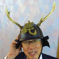 Harumi Yonemura, a board member of the Japan Gibier Promotion Association, dons his samurai helmet complete with its set of deer antlers. | KIT NAGAMURA