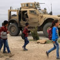 Children walk to school as U.S. troops patrol near the Turkish border in Hasakah, Syria, on Nov. 4. In a sudden policy reversal, President Donald Trump sent out a tweet last week saying the U.S. will pull its forces out of the country. | REUTERS
