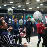 An applicant for the 2019 Rugby World Cup's volunteer program catches a rugby ball during an interview session in Tokyo on Monday. RYUSEI TAKAHASHI