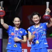 Misaki Matsutomo (left) and Ayaka Takahashi celebrate after winning the badminton World Tour Finals championship in women's doubles on Sunday in Guangzhou, China. | KYODO