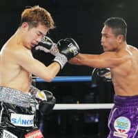 Kazuto Ioka (left) receives a punch from Donnie Nietes during their WBO super flyweight title bout in Macao on Sunday. Nietes won by decision. | KYODO
