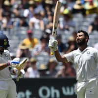India batsman Cheteshwar Pujara (right) celebrates reaching a century with team captain Virat Kohli on Thursday during day two of the third test with Australia in Melbourne, Australia. | AFP-JIJI