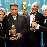 Muhammad Ali and George Foreman pose with producers Leon Gast (left) and David Sonenberg after their film 'When We Were Kings' won the Academy Award for Best Documentary Feature in 1997. | KYODO