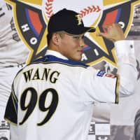 New Fighters player Wang Po-jung poses for photos during a news conference on Wednesday in Taipei. | KYODO