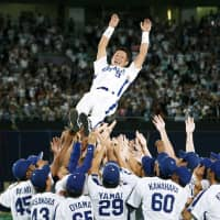 Former Dragons infielder Kazuyoshi Tatsunami is lifted into the air during his retirement ceremony on Sept. 30, 2009, at Nagoya Dome. | KYODO